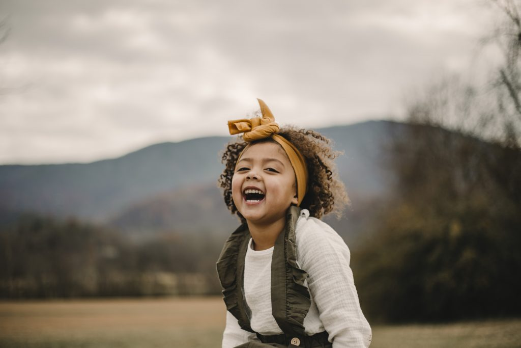 little girl with yellow bow laughing